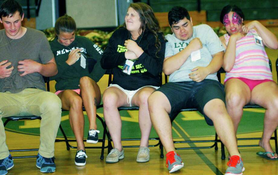 Graduates experience a sudden need to scratch while participating in hypnotist Dan LaRosa's show during the New Milford High School Grad Party, June 21-22, 2014 at NMHS. Photo: Norm Cummings / The News-Times