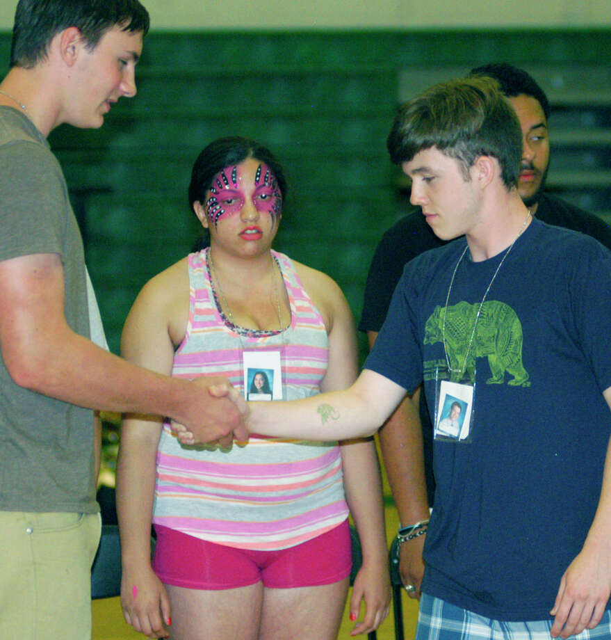 Graduates shake hands, and then can't separate their hands while participating in hypnotist Dan LaRosa's show during the New Milford High School Grad Party, June 21-22, 2014 at NMHS. Photo: Norm Cummings / The News-Times