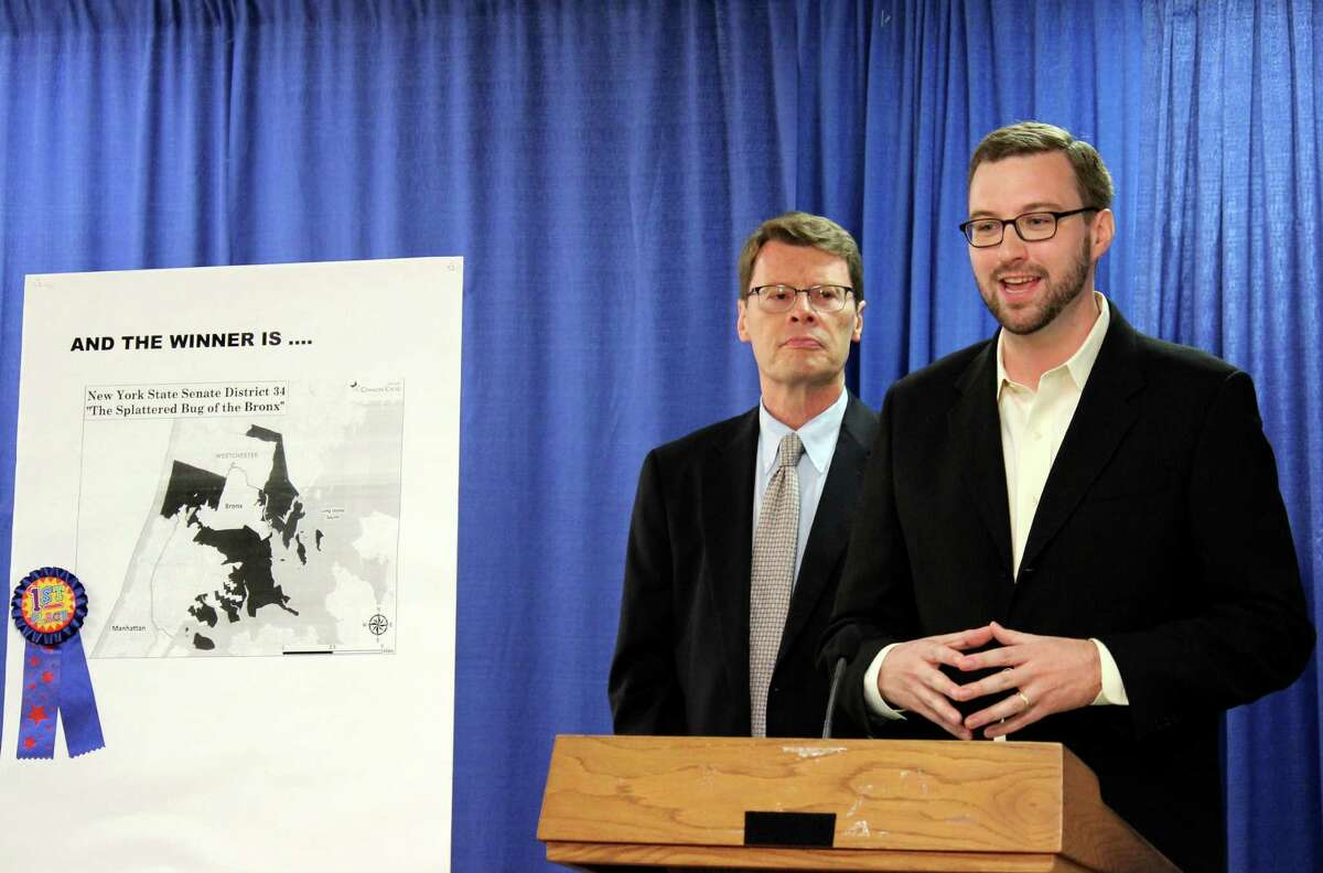 NYPIRG legislative director, Blair Horner, left, and Effective NY executive director, Jesse Laymon, right, speak during a news conference where they criticized the state?s legislative redistricting process Monday, June 23, 2014, at the Legislative Office Building in Albany N.Y. During the event NYPIRG awarded Senate District 34, chart displayed left, as the most gerrymandered district in the state. (Selby Smith / Special to the Times Union)