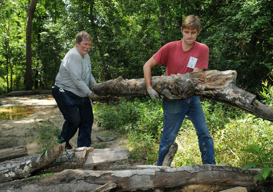 T.W. Garrett, from left, a resident of Plumb Grove and a Bayou Land Conservancy member, and Trey Price, of The Woodlands (77381) and a Bayou Land Conservancy board member, build a roadblock to an illegal ATV access point during a Spring Creek Greenway cleanup. Photo: Jerry Baker, For The Chronicle