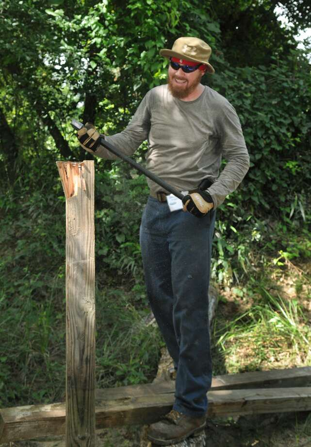 James Fosson, from left, of Spring (77379), a Bayou Land Conservancy ambassador, uses an axe to help build a roadblock to an illegal ATV access point during a Spring Creek Greenway cleanup. Photo: Jerry Baker, For The Chronicle