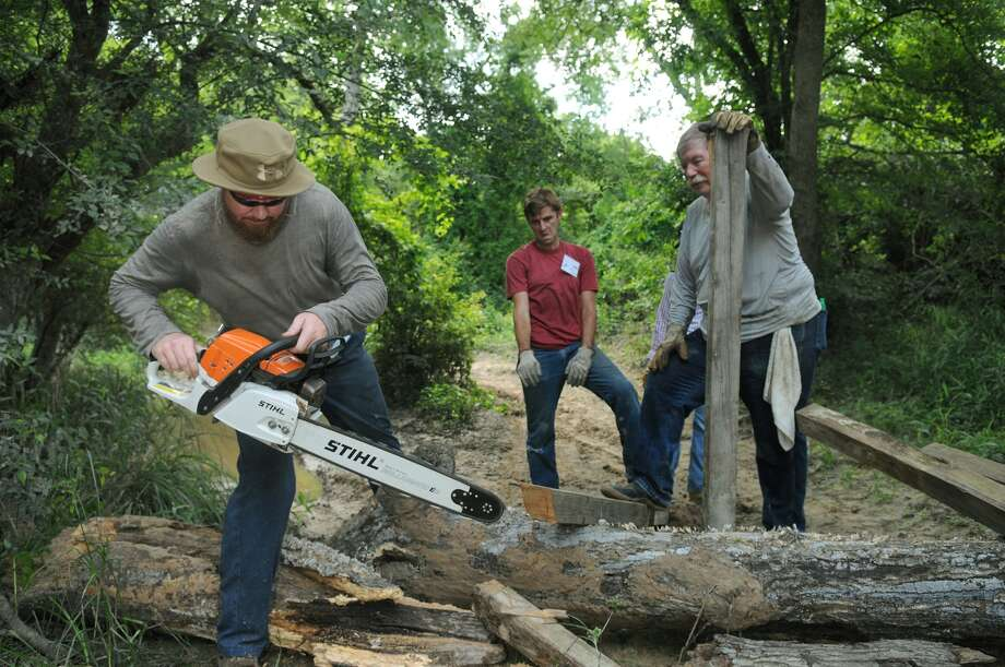 James Fosson, from left, of Spring (77379), a Bayou Land Conservancy ambassador, with help from Trey Price, of The Woodlands (77381) and a Bayou Land Conservancy board member, and T.W. Garrett, a resident of Plumb Grove Grove and a Bayou Land Conservancy member, uses a chain saw to help build a roadblock to an illegal ATV access point during a Spring Creek Greenway cleanup. Photo: Jerry Baker, For The Chronicle