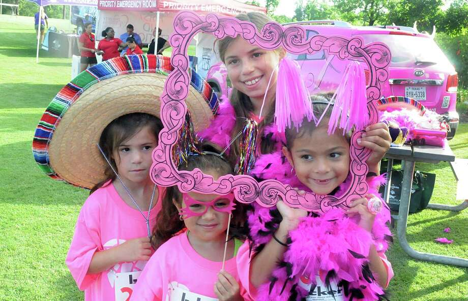 Karla Hernandez, Lucy Martinez, Paula Hernandez, and Pia Martinez, all of The Woodlands, play with photography props during The Pink 5K walk/Run, against breast cancer, at Creekside Park in The Woodlands. The run will benefit the Breast Cancer Charities of America. Photograph by David Hopper Photo: David Hopper, For The Chronicle / freelance