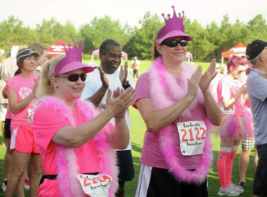 Laura Moore and Rhonda Sheldon, both of The Woodlands, applaud the speakers during The Pink 5K walk/Run, against breast cancer, at Creekside Park in The Woodlands. The run will benefit the Breast Cancer Charities of America. Photograph by David Hopper Photo: David Hopper, For The Chronicle / freelance