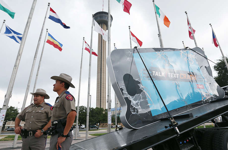 DPS Troopers Anthony Flores (left) and Orlando Moreno stand next to a huge crashed cellphone outside the Institute of Texan Cultures that's part of the Talk, Text, Crash campaign. Photo: Photos By Jerry Lara / San Antonio Express-News / © 2014 San Antonio Express-News