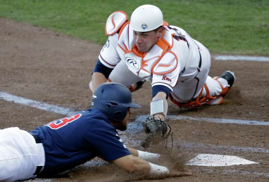 Vanderbilt first baseman Zander Wiel, front, slides safely into home plate for a run against Virginia catcher Nate Irving in the third inning of game one of the best-of-three NCAA baseball College World Series finals in Omaha, Neb., Monday, June 23, 2014. (AP Photo/Nati Harnik) Photo: Nati Harnik, Associated Press / AP