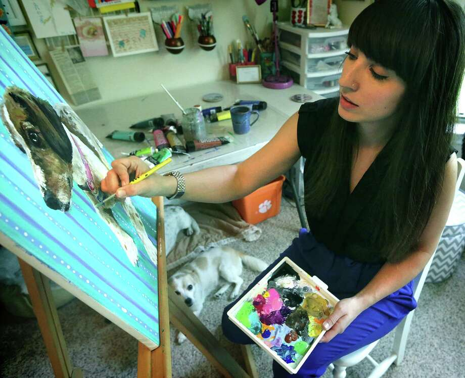 Rachael Marie Bower paints portraits of pets — some of them in costume. Here, she works on an image of her dog Sadler. Photo: Bob Owen / San Antonio Express-News / © 2012 San Antonio Express-News
