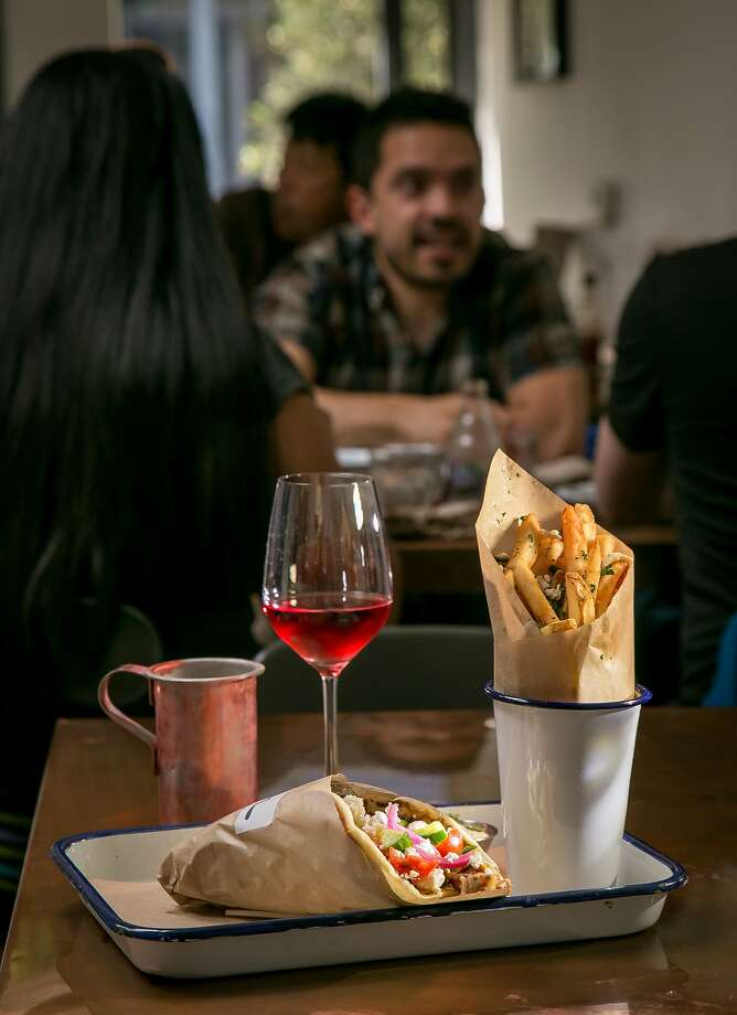The pork shoulder sandwich ($10) with Greek fries ($4) and a Greek rosé wine ($10). Photo: John Storey, Special To The Chronicle