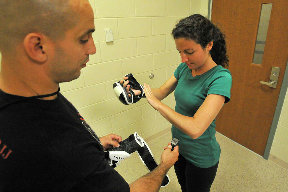 Greenwich Time reporter Brittany Lyte puts on her training gloves as the instructor, Officer Jeff Morris, wirelessly checks her resting pulse rate before going into a live scenario during a women's self defense class at the Greenwich Police Department in Greenwich, Conn., on Monday, June 23, 2014. Photo: Jason Rearick / Stamford Advocate