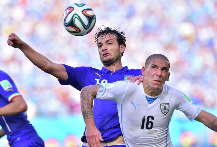 Italy's midfielder Marco Parolo (L) and Uruguay's defender Maximiliano Pereira vie during the Group D football match between Italy and Uruguay at the Dunas Arena in Natal during the 2014 FIFA World Cup on June 24, 2014.  AFP PHOTO / GIUSEPPE CACACEGIUSEPPE CACACE/AFP/Getty Images Photo: GIUSEPPE CACACE, AFP/Getty Images / AFP