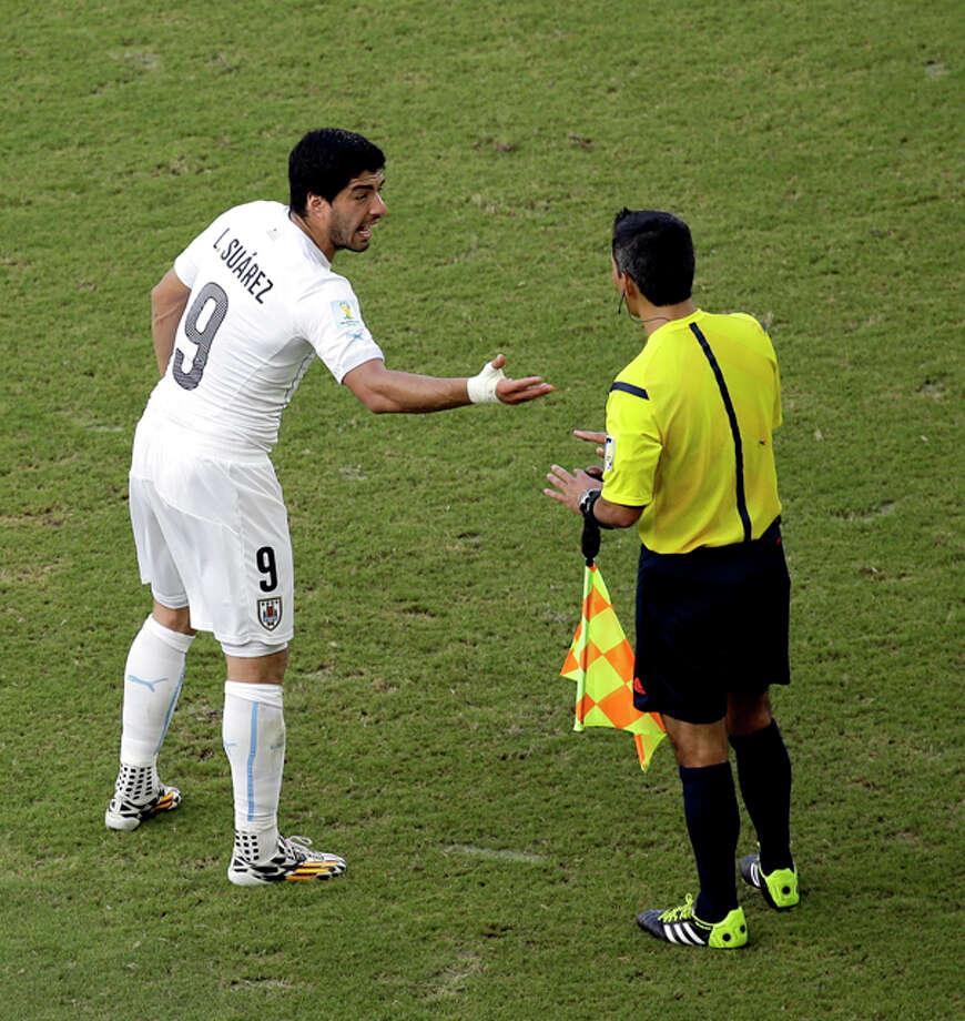 Uruguay's Luis Suarez talks with a referee during the group D World Cup soccer match between Italy and Uruguay at the Arena das Dunas in Natal, Brazil, Tuesday, June 24, 2014. (AP Photo/Hassan Ammar) Photo: Hassan Ammar, Associated Press / AP