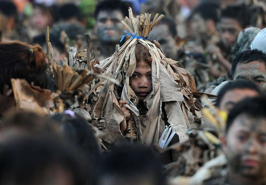 Keep your fronds close: Devotees covered in mud and wearing costumes made from banana leaves attend Mass during a 
