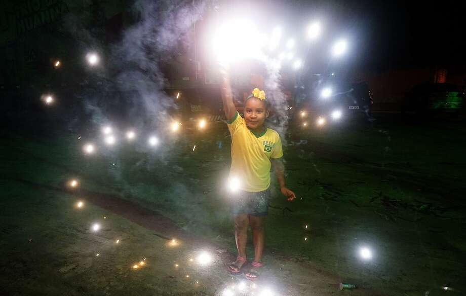 Round two, here we come:A little girl plays with fireworks after watching Brazil beat Cameroon on TV 