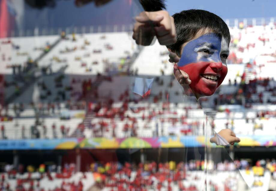 Who's a head? A young Chilean fan looks onto the pitch during the Netherlands-Chile match at Itaquerao Stadium in Sao Paulo. Photo: Felipe Dana, Associated Press