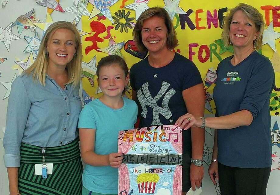 Tokeneke School music teacher Rebecca Parnoff, from left, Assistant Principal Kathy Schultz and Principal Mary Michelson congratulate poster contest winner and student Lily Childs. Photo: Contributed Photo, Contributed / Darien News
