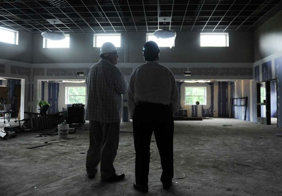 Danbury Superintendent of Construction Services Tom Hughes, left, and Danbury Superintendent of Schools Dr. Sal Pascarella look upon the media center at the new Westside Middle School Academy in Danbury, Conn. Tuesday, June 24, 2014.  Construction crews are just putting some finishing touches on the building, which will be ready for next year's school year.  Westside will be a magnet school with two academies - STEM (science, technology, engineering, math) and global studies. Photo: Tyler Sizemore / The News-Times