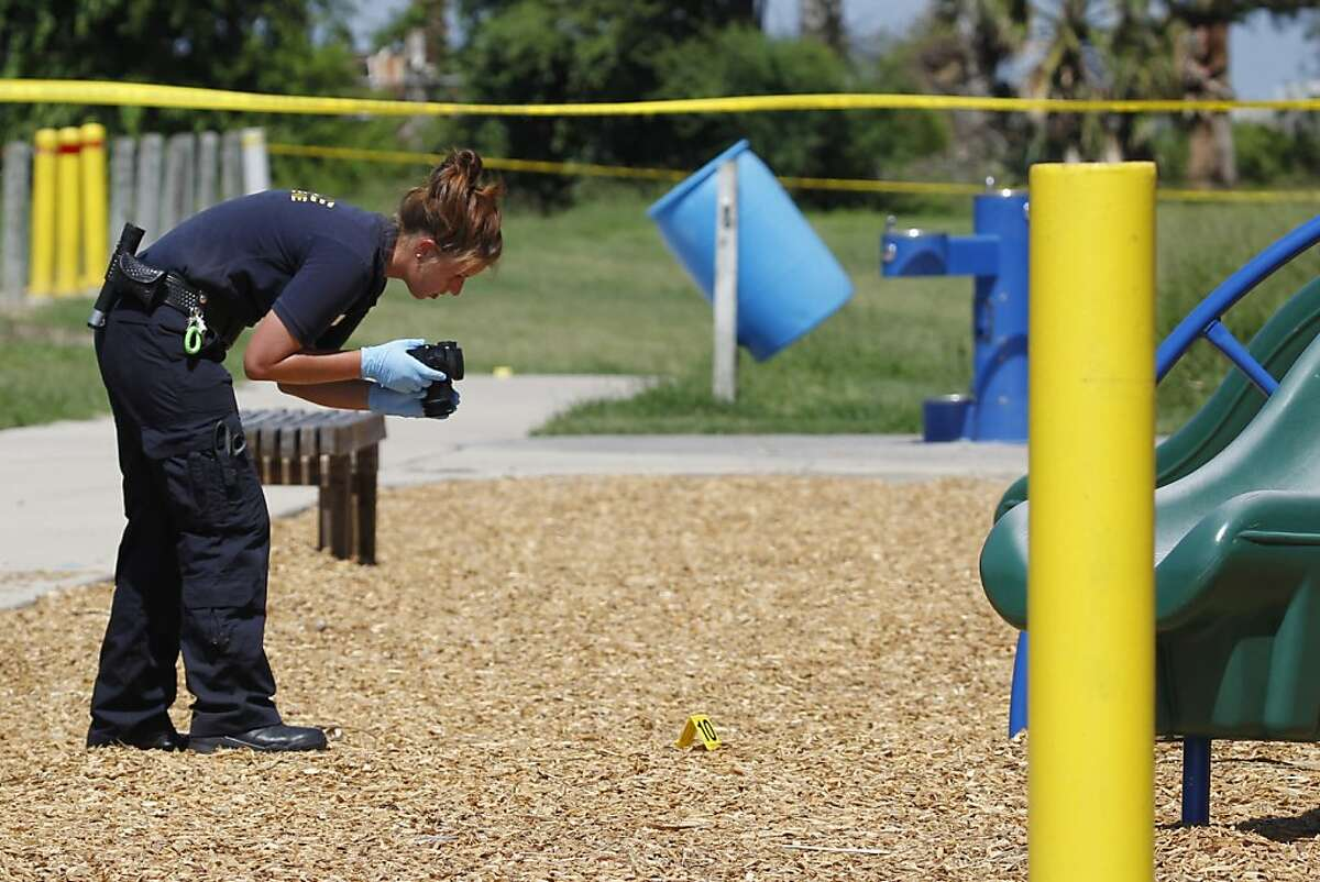 A crime scene investigator takes pictures of an evidence marker near some playground equipment Saturday, June 23, 2012 at Violet Andrews Park in Portland, Texas. Gay rights groups have called for a thorough police investigation into the fatal shooting of a teenage woman and wounding of her girlfriend in the park. Portland police say they don't know the motive for the shooting Friday night, June 22, 2012, that killed 19-year-old Mollie Olgin and wounded 18-year-old Mary Kristene Chapa in Violet Andrews Park.