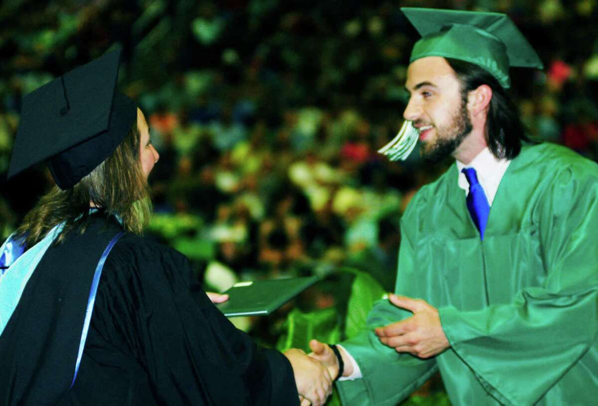Andrew McGuire happily accepts congratulations and his diploma from Board of Education chairwoman Daniele Shook during New Milord High School's 2014 commencement ceremony at the O'Neill Center on the campus of Western Connecticut State Universityn in Danbury. June 21, 2014