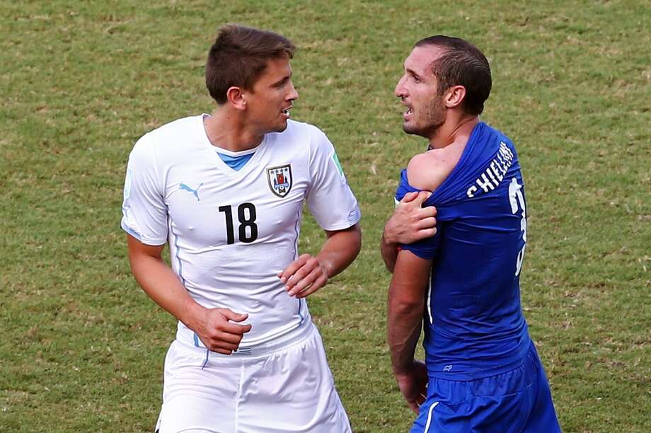 Giorgio Chiellini of Italy pulls down his shirt after a clash with Luis Suarez of Uruguay (not pictured) as Gaston Ramirez of Uruguay looks on during the 2014 FIFA World Cup Brazil Group D match between Italy and Uruguay at Estadio das Dunas on June 24, 2014 in Natal, Brazil. Photo: Julian Finney, Getty Images
