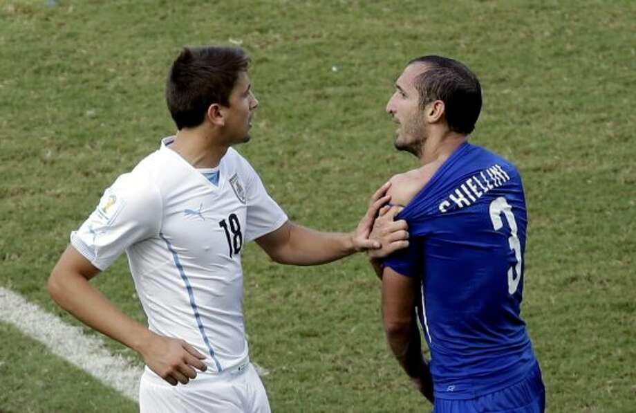 Italy's Giorgio Chiellini (3) complains after Uruguay's Luis Suarez ran into his shoulder with his teeth during the group D World Cup soccer match between Italy and Uruguay at the Arena das Dunas in Natal, Brazil, Tuesday, June 24, 2014. Photo: Hassan Ammar, Associated Press