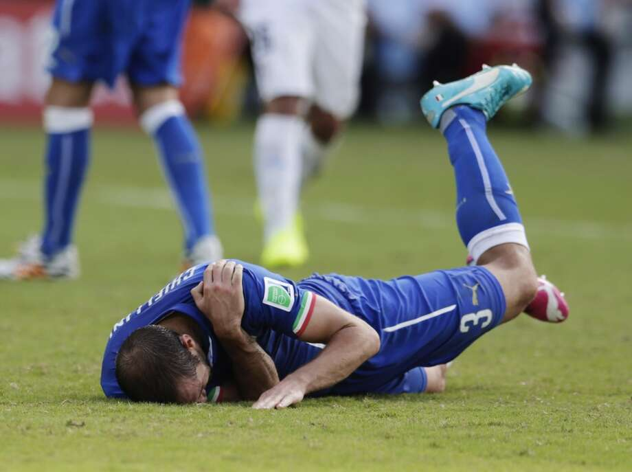 Italy's Giorgio Chiellini holds his shoulder after Uruguay's Luis Suarez ran into it with his teeth during the group D World Cup soccer match between Italy and Uruguay at the Arena das Dunas in Natal, Brazil, Tuesday, June 24, 2014. Photo: Petr David Josek, Associated Press