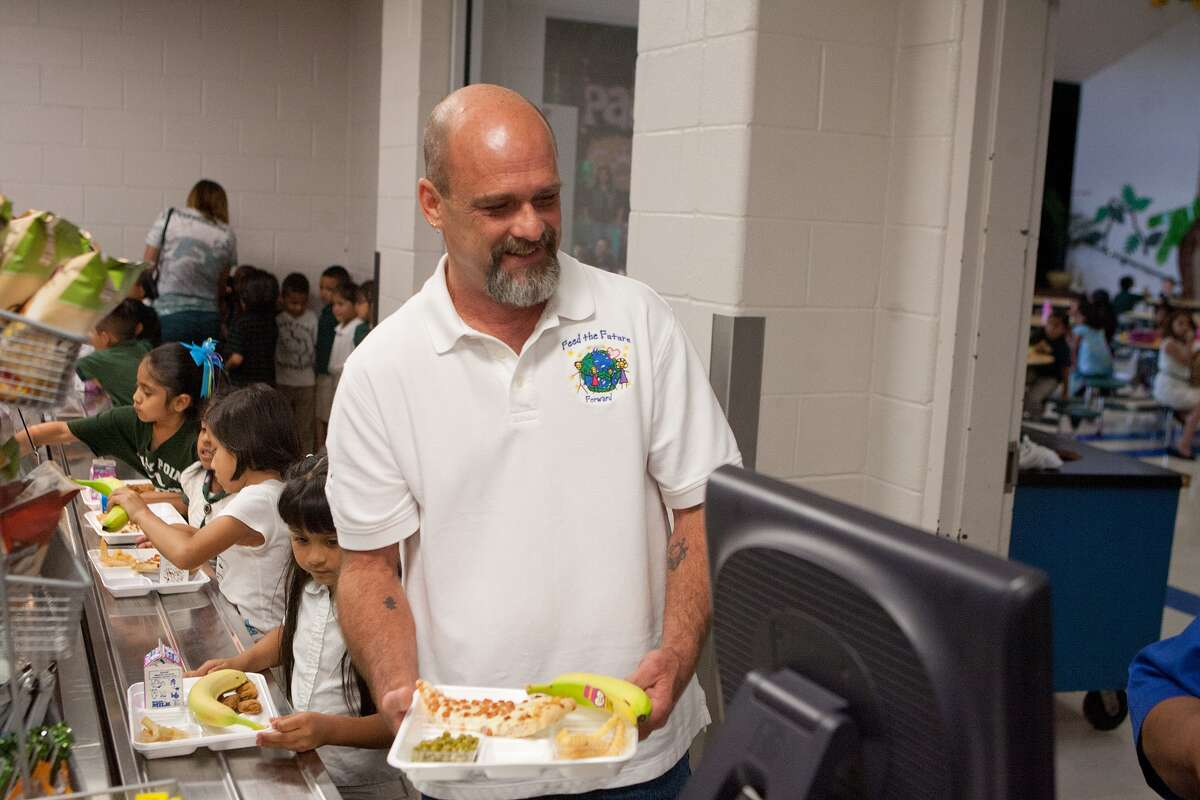 Kenny Thompson gets a meal in the lunch line at Piney Point Elementary School, one of the campuses where Thompson's Feed The Future Forward provides funds to help buy lunch for pupils who lack money.