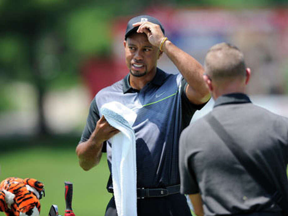 Tiger Woods looks on from the driving range as he practices at the Quicken Loans National golf tournament, Tuesday, June 24, 2014, in Bethesda, Md. Photo: Nick Wass, AP / FR67404 AP