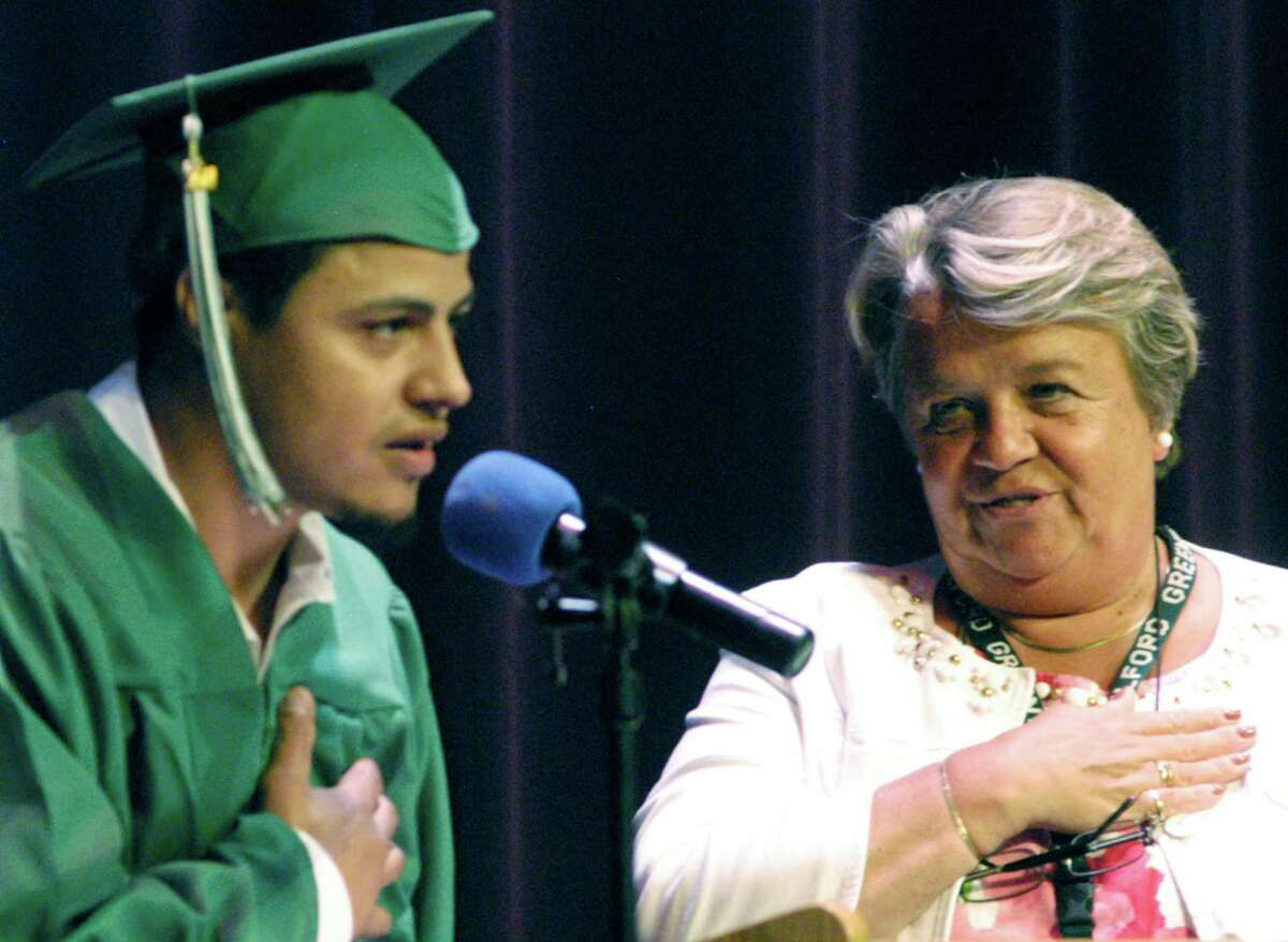 Giovanie Semidey leads the Pledge of Allegiance for adult education director Dr. Joanne Brogis, his classmates and others attending New Milford adult education commencement exercises at the school, June 11, 2014.