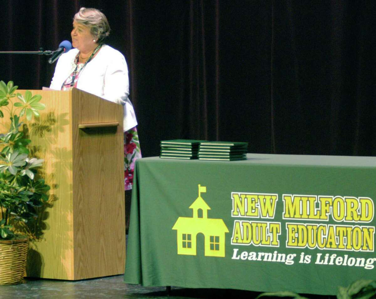 Diplomas await the soon-to-be graduates as program director Dr. Joanne Brogis addresses those in attendance at New Milford adult education commencement exercises at the school, June 11, 2014.