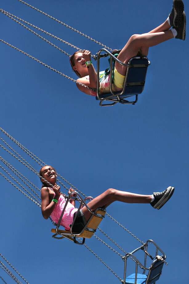 Savanna Nelson, top, and Jaida Carr ride the Wave Swinger at the Alameda County Fair in Pleasanton. Photo: Kevin N. Hume, The Chronicle