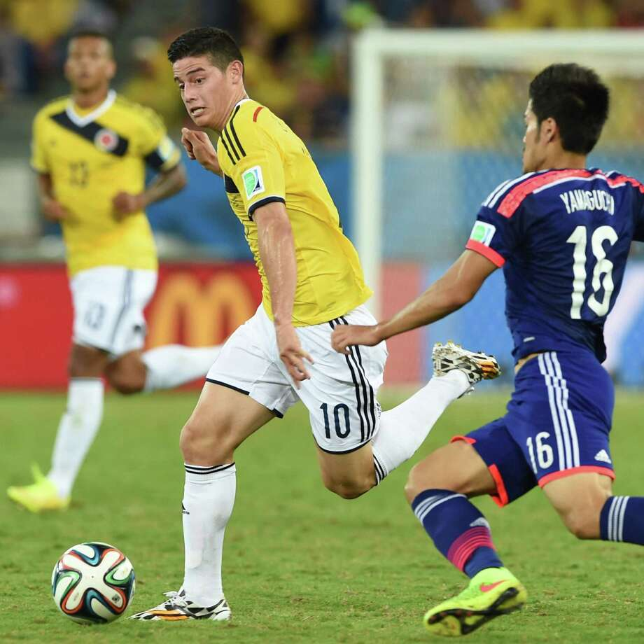 Colombia's midfielder James Rodriguez (L) and Japan's midfielder Hotaru Yamaguchi vie for the ball during a Group C football match between Japan and Colombia at the Pantanal Arena in Cuiaba during the 2014 FIFA World Cup on June 24, 2014.  AFP PHOTO / TOSHIFUMI KITAMURATOSHIFUMI KITAMURA/AFP/Getty Images Photo: TOSHIFUMI KITAMURA, AFP/Getty Images / AFP