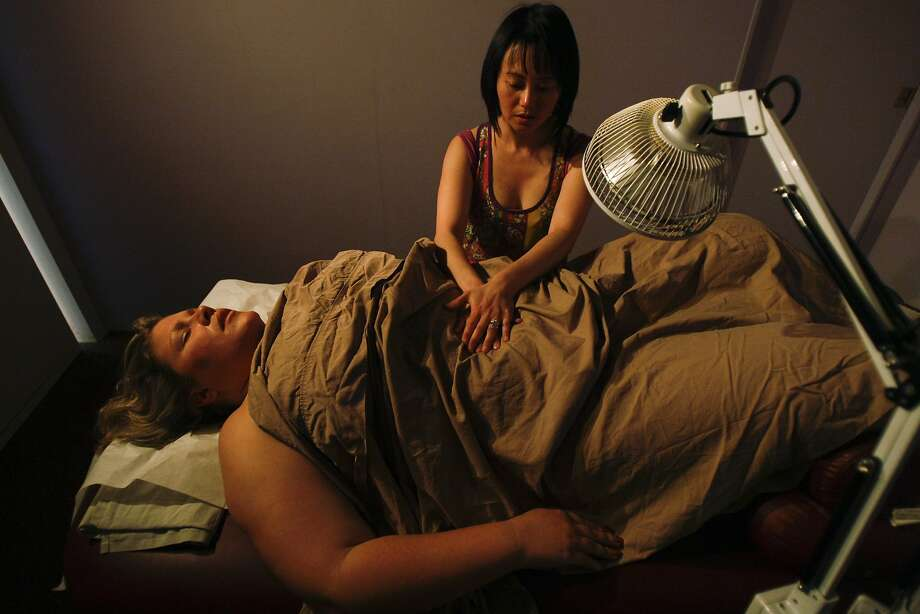 Wei Chang massages Natalie DiMarco, diagnosed with lung cancer in 2009 at the age of 32, prior to cupping treatment. Photo: Craig Hudson, The Chronicle