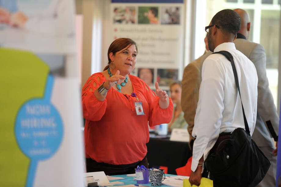 From left, Misty Hanks with Met Head Start talks to Vincent Matthews during the Beaumont Independent School District's job fair at the BISD Media Center on Tuesday. The job fair was designed to help relocated district employees effected by the reduction in force. Photo taken Tuesday, June 24, 2014  Guiseppe Barranco/@spotnewsshooter Photo: Guiseppe Barranco, Photo Editor