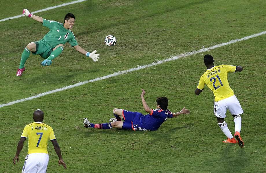 Jackson Martinez (right) puts one of his two goals past Japan's keeper, Eiji Kawashima, in Colombia's 4-1 Group C victory. Photo: Shuji Kajiyama, Associated Press