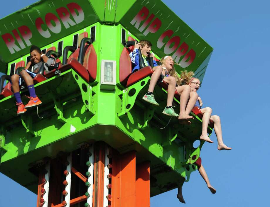 Newtown kids, from left, Jalen Minter, 12, Bryce Benson, 12, Ella Marsh, 11, and Shaylen Ames, 11, ride down the vertical drop of the Rip Cord at the St. Rose Carnival 2014 at St. Rose of Lima Church in Newtown, Conn. Tuesday, June 24, 2014.  The carnvial featured games and rides for children and lots of food from many local vendors.  The carnival kicked off Tuesday, but continues through Saturday, June 28 starting at 6 p.m. each night. Photo: Tyler Sizemore / The News-Times