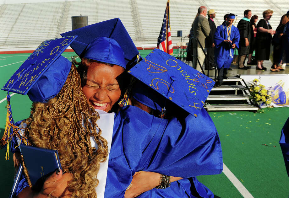 Graduate Jesica Lee, center, gets big hugs from her fellow classmates, during Warren Harding High School's 88th Annual Commencement Ceremony held at Central High School's Kennedy Stadium in Bridgeport, Conn. on Tuesday June 24, 2014. Photo: Christian Abraham / Connecticut Post