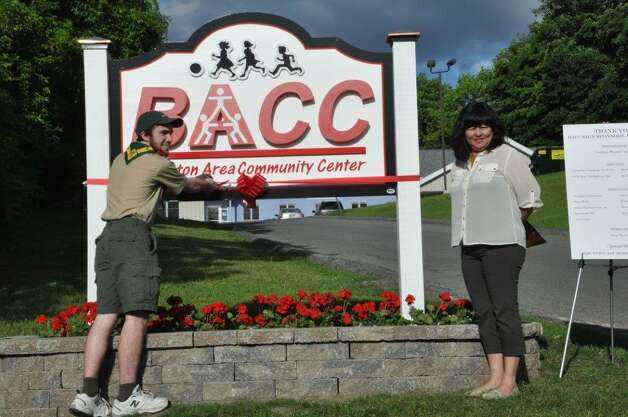 Life Scout Michael Hosek of Troop 1 cut the ribbon on the Ballston Area Community Center sign as center Director Kathi Leigh looks on. As his Eagle Scout project, Hosek managed the construction of the sign so it could be seen from Milton Avenue. A ribbon-cutting ceremony took place at First Friday festivities on June 20. (Submitted photo)