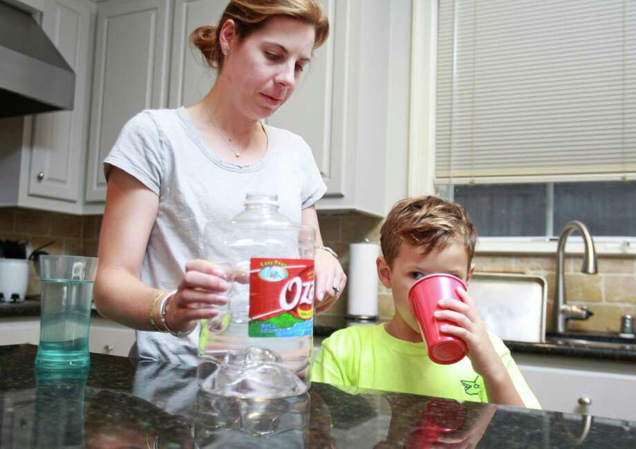 "Kara Hilliard gives her son, Henry Hilliard, 7, a drink of bottled water Tuesday at their Galleria-area home. Tap water, she says, ""tastes like algae."" Photo: Melissa Phillip, Staff / © 2014  Houston Chronicle"