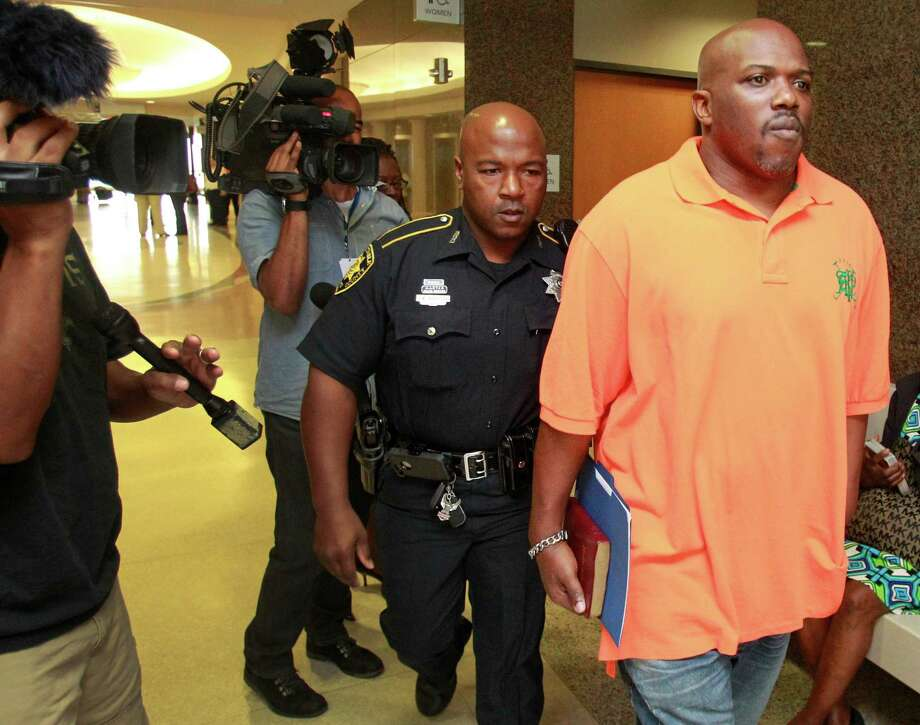 Clifford Hall, right, surrendered himself to authorities Tuesday after exhausting his appeals options in a child support case in which he says his employer, AT&T, withheld the incorrect amount for months. Photo: Melissa Phillip, Staff / © 2014  Houston Chronicle