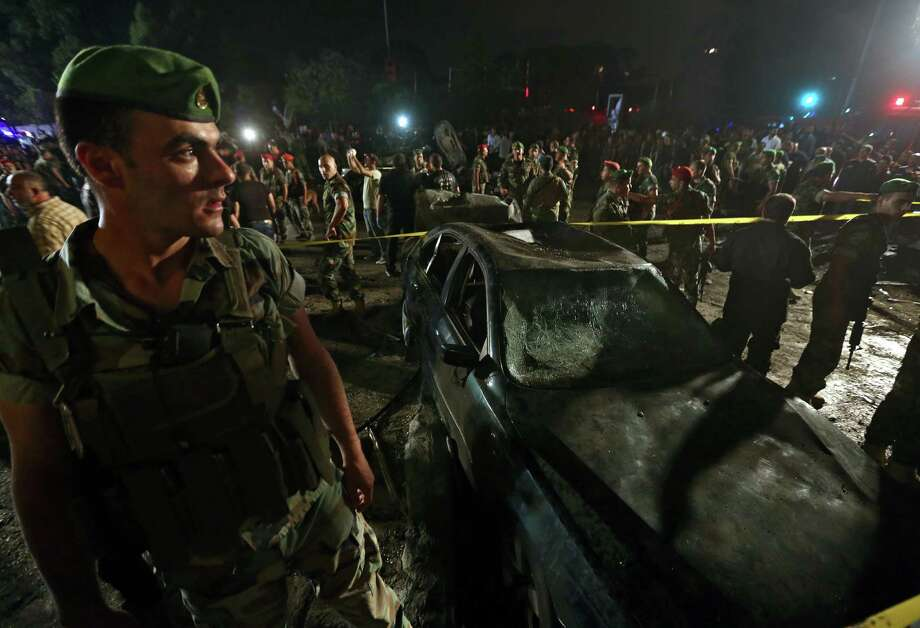 Lebanese soldiers and citizens gather Tuesday at the site of a car bombing in a southern suburb of Beirut. The explosion, which left one person dead and injured 20, was the second overnight bombing this week. Photo: Bilal Hussein, STF / AP