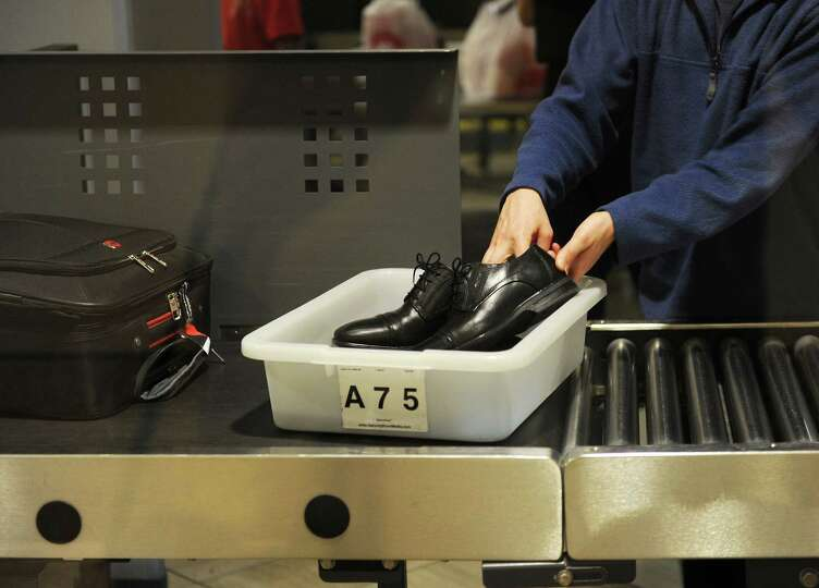 An air traveler places his shoes in a bin before passing through the Transportation Security Adminis