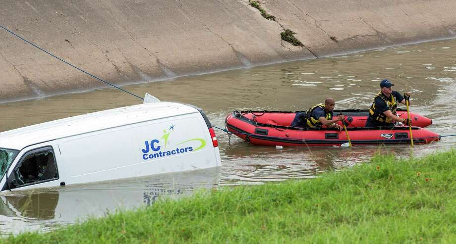 Searchers try to find the driver of a van that went airborne off Cullen and landed in Brays Bayou on Tuesday. Photo: Craig Hartley, For The Chronicle / Photos by Craig Hartley