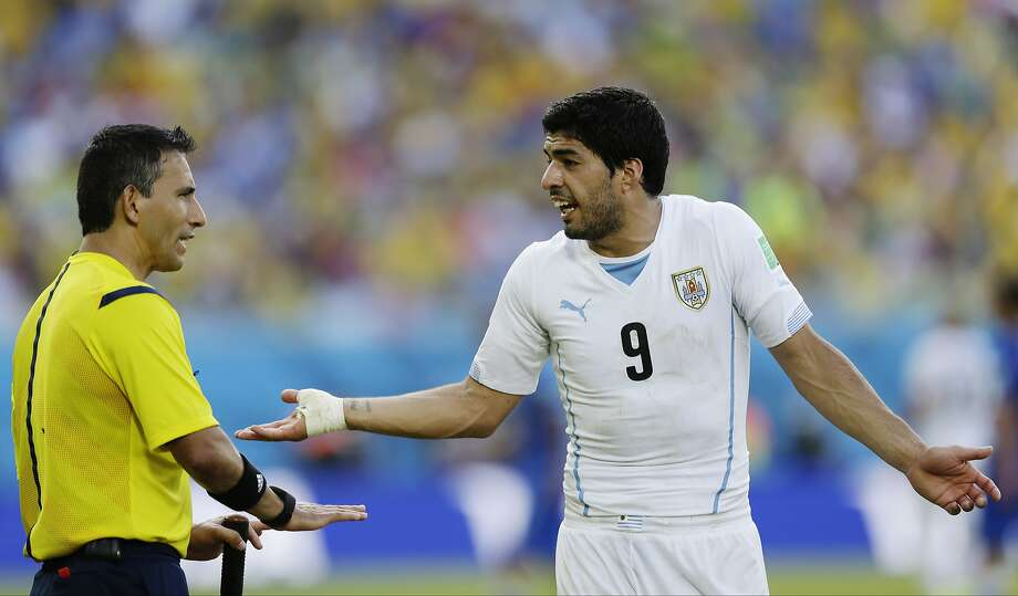 Uruguay forward Luis Suarez, above, right, who's been involved in three biting incidents in the past four years, argues with referee Marco Rodriguez. Photo: Ricardo Mazalan, Associated Press