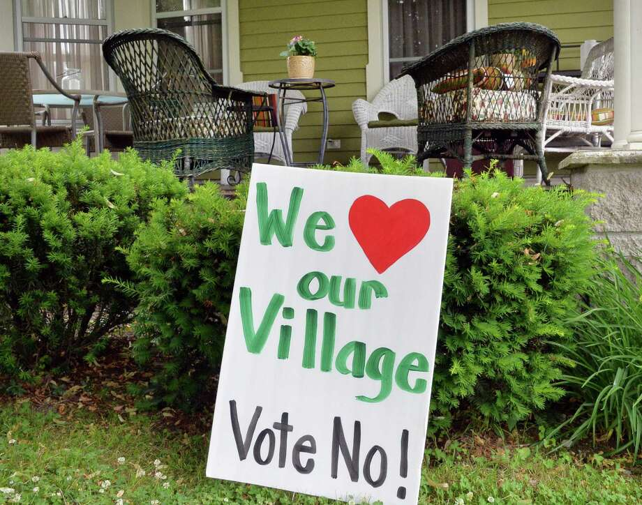 A sign on the lawn of a Bleeker Street home as residents go to the polls to vote on a proposal to dissolve the village of Greenwich Tuesday, June 24, 2014, in Greenwich, NY. If passed, the village would merge with the towns of Greenwich and Easton.  (John Carl D'Annibale / Times Union) Photo: John Carl D'Annibale / 00027487A