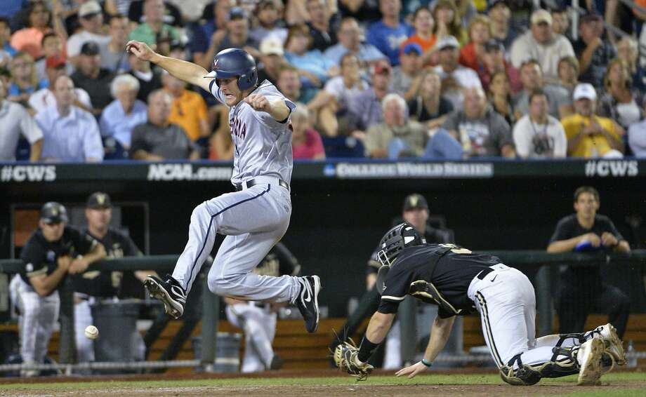 Virginia's Joe McCarthy (31) jumps as he scores against Vanderbilt catcher Jason Delay (5) in the seventh inning of Game 2 of the best-of-three NCAA baseball College World Series finals in Omaha, Neb., Tuesday, June 24, 2014. (AP Photo/Ted Kirk) Photo: Ted Kirk, Associated Press