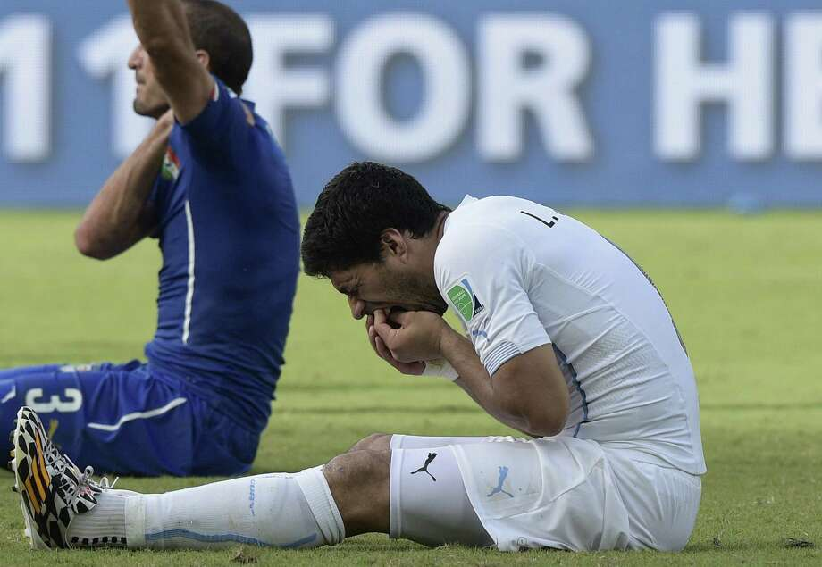 Uruguay's Luis Suarez holds his mouth after what Giorgio Chiellini (background) claimed was a bite to the Italian's shoulder. Photo: Daniel Garcia / AFP / Getty Images / AFP