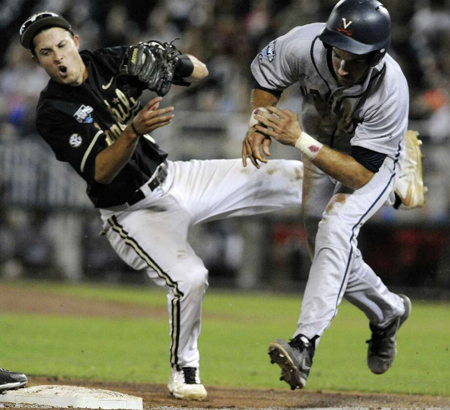 Vanderbilt third baseman Tyler Campbell (left) and Virginia's Mike Papi collide during a rundown between third and home in the ninth inning. Papi was out. Photo: Eric Francis / Associated Press / FR9944 AP