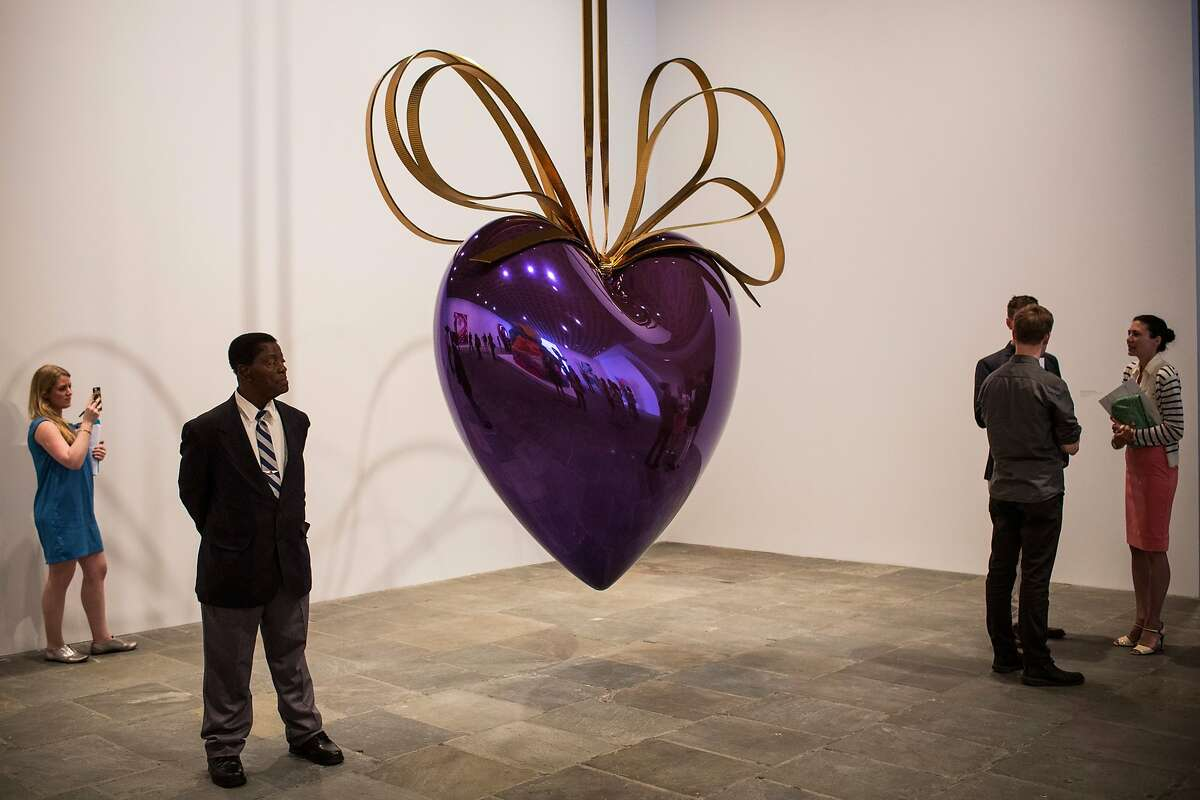 NEW YORK, NY - JUNE 24: People look at the art work of Jeff Koons during a media preview of his retrospective at The Whitney Museum of American Art on June 24, 2014 in New York City. Nearly the entire museum will be filled with four decades of Koons' work; it opens to the public June 27th. (Photo by Andrew Burton/Getty Images)