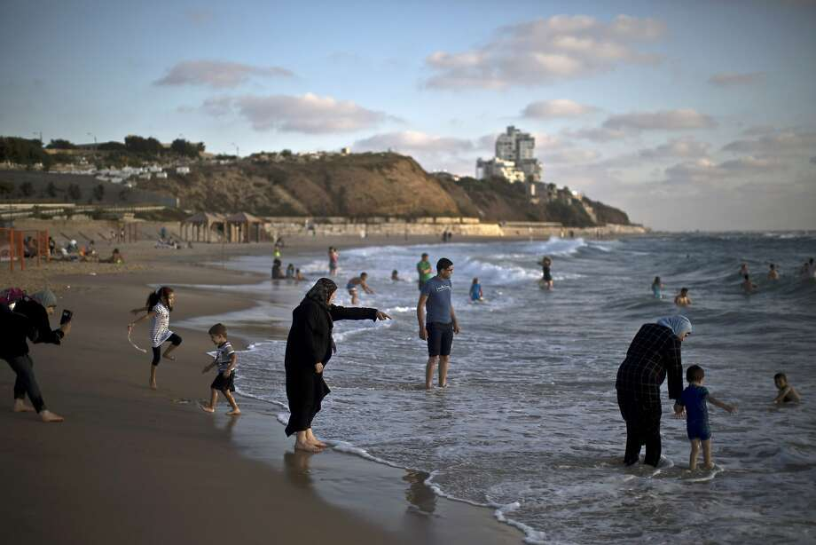 In This Monday, June 23, 2014, photo, an Arab family enjoys at the beach of the Mediterranean sea, in Jaffa, a mixed Jewish and Arab part of Tel Aviv, Israel. (AP Photo/Muhammed Muheisen) Photo: Muhammed Muheisen, Associated Press