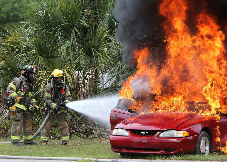 From left, firefighters Lt. David Jernigan and Jason Tate put out a car fire during a training exercise in Panama City, Fla. on Tuesday, June 24, 2014. (AP Photo/The News Herald - Panama City, Fla., Andrew Wardlow) Photo: Andrew Wardlow, Associated Press